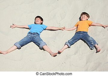 Two children lying nearby on sand