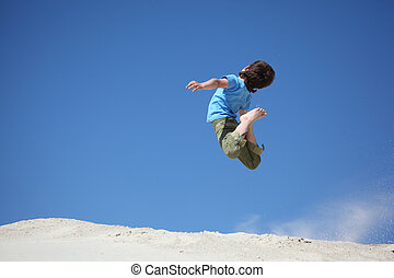 boy jumps on sand