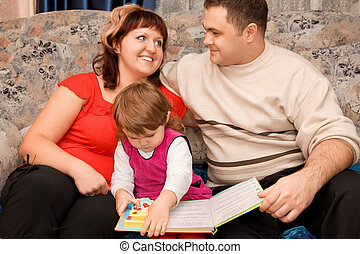 Married couple and  little girl read  book in a cosy room