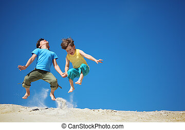 Two boys jump on sand