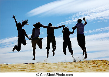 group of friends jumps on sand, rear view, silhouette