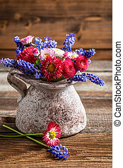 Spring flowers in a vase on wooden table