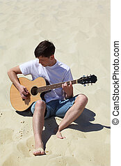 guy plays guitar sitting on sand