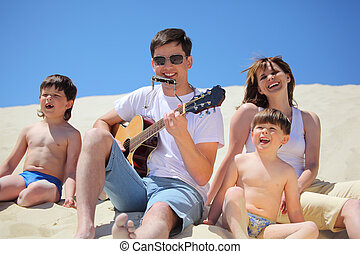 guy in sunglasses plays guitar and  lip accordion  with children and girl singing song sitting on sand