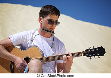 guy in sunglasses plays guitar and  lip accordion sitting on sand