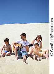 guy in sunglasses plays guitar and  lip accordion  with children and girl sitting on sand
