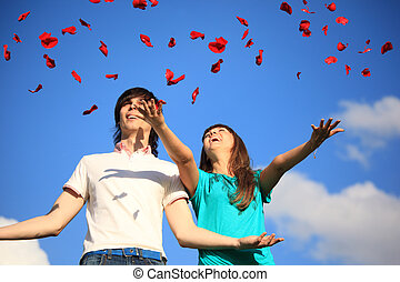 young pair scatters petals of roses against sky
