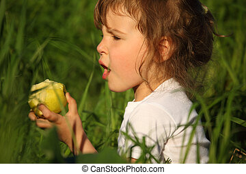 girl eats green apple in grass