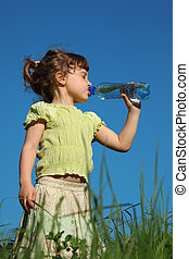 girl standing in grass drinks water from plastic bottle