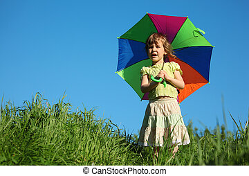 girl with  multicoloured umbrella in grass
