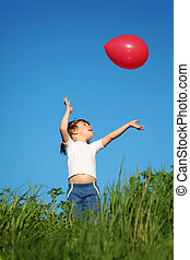 little girl plays with red balloon in grass