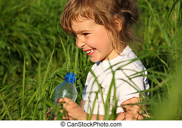 smiling little girl in grass with plastic bottle