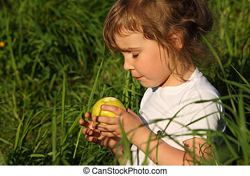 little girl in grass with green apple