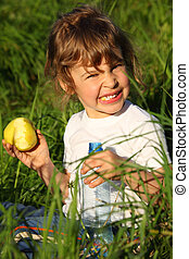 girl with plastic bottle eats green apple in grass