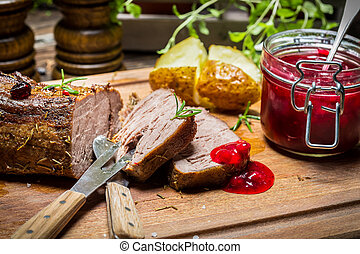 Venison with rosemary served with cranberry sauce