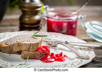 Venison with cranberry sauce on white plate
