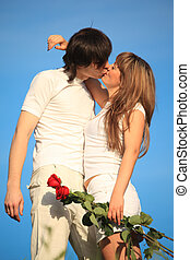 girl with bouquet of roses kisses guy  against sky