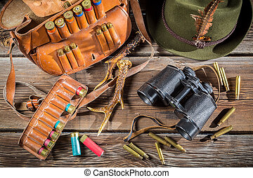 Bag with bullets, binoculars and hat in a hunting lodge