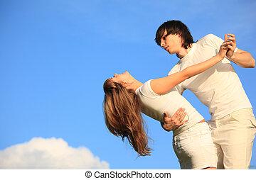 guy holds girl for waist against sky
