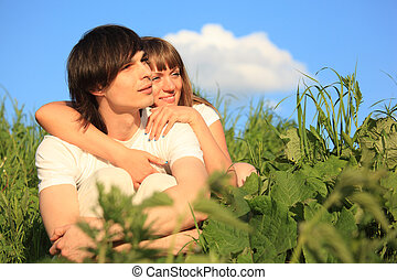 girl embraces guy behind for among a grass
