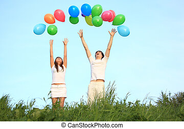 girl and guy start multicoloured balloons in sky