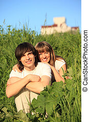 girl embraces guy behind for shoulders among grass
