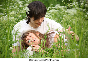 girl lies in lap of guy sitting in grass