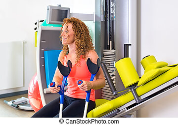 Patient with crutches sitting on weight machine - Smiling...