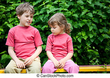 The boy and the girl sit on a bench in park