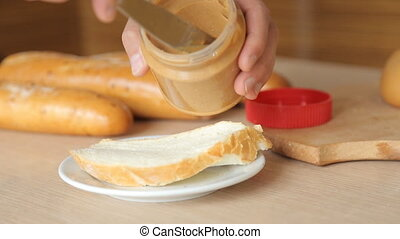 Tasty creamy peanut butter being spread on white bread -...