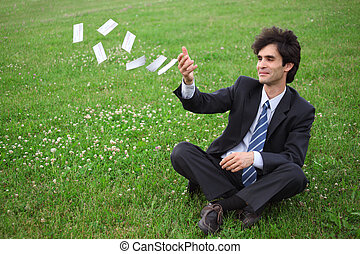businessman sitting on the meadow and throwing paper cards