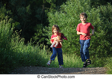 boy and girl run with doll in park