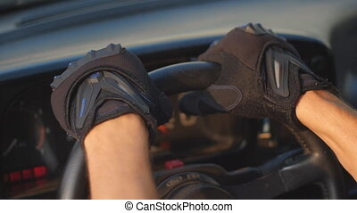 man holding hands on the steering wheel of the car and...