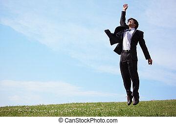 businessman jumping on grass
