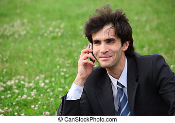 Businessman sits on the meadow and speaks over mobile