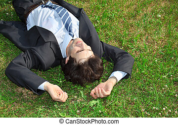 businessman lies on back on grass