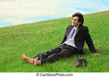 Businessman sitting on the meadow barefoot