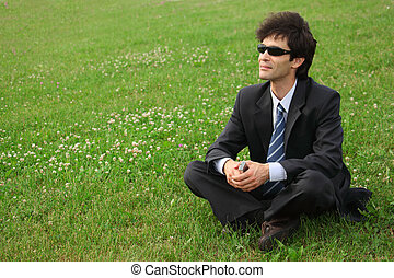 Businessman sitting on the meadow