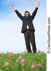 Businessman standing with hands up on the meadow