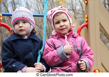 Two thoughtful girls on playground
