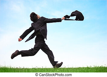 Businessman running on the meadow with bag