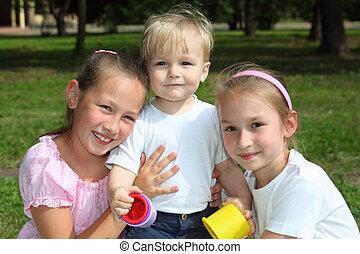 three children in park in summer