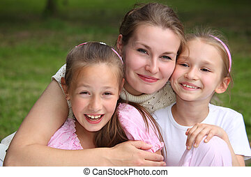 Mother embraces daughters outdoor in summer