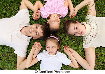 Parents with children lying on grass, view from top, head to head,  having joined hands
