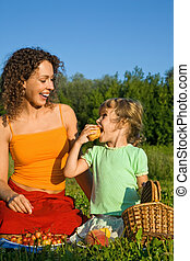 pretty Little Girl and Young Women eats fruits on picnic