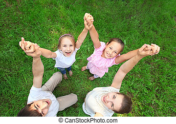 Parents with children stand having joined hands and having lifted them, top view, wide angle