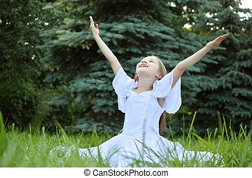 girl in white dress sits on lawn with lifted hands