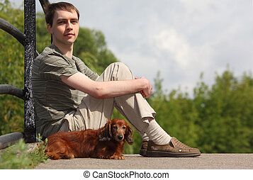 young man and his dachshund sits outdoor in summer