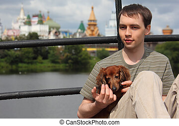 young man holds dachshund on hands outdoor in summer