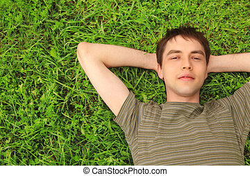 teenager lies on grass - young man lies on grass
